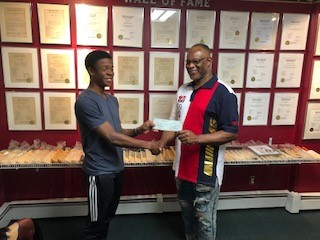 President Caswell Sewell presented Stephan Pink check for 2019 tuition at UWI